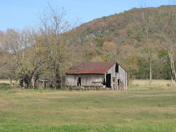 Open fields and mountain views surround this old country barn